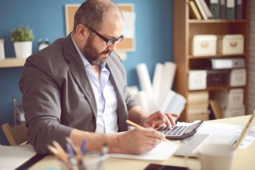 Male Trust Administrator Calculating Taxable Income and Accounting Income