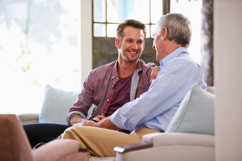 Senior Father With Adult Son Talking About Estate Plan