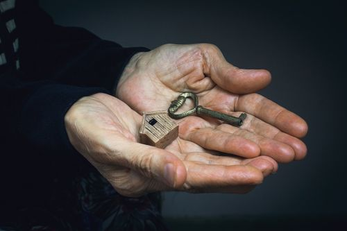 Older Woman's Hands Holding House Key - Gave Up House Under Undue Influence
